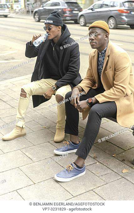 two fashionable male friends resting at bench and drinking water from plastic bottle at street in city Munich, Germany