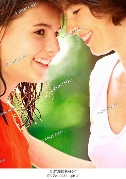 Side profile of a teenage girl with her mother smiling