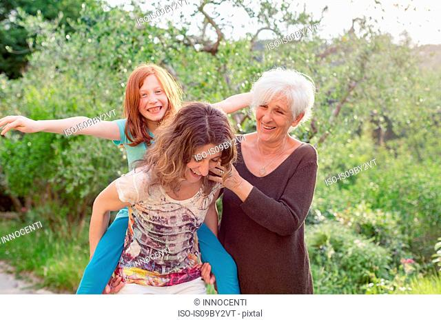 Girl getting piggyback with mother and grandmother in garden