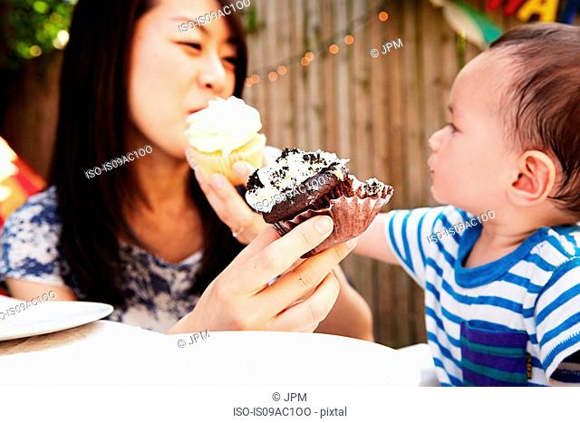 Mother and son feeding each-other cupcakes