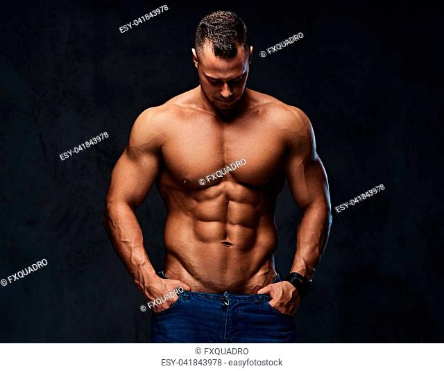 Studio portrait of shirtless muscular male in a jeans over grey background