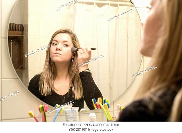Tilburg, Netherlands. Young adult caucasian woman doing her daily make-up in front of a bathrom mirror