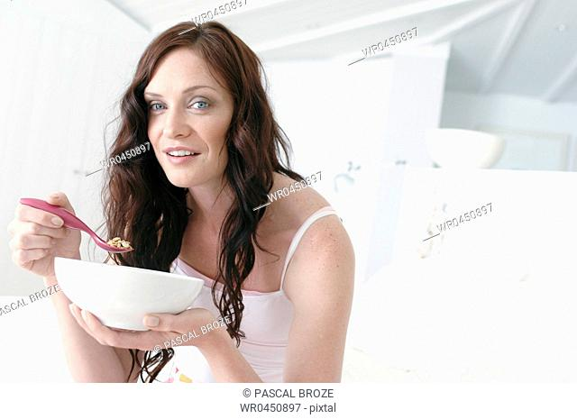 Portrait of a mid adult woman holding a bowl and a spoon