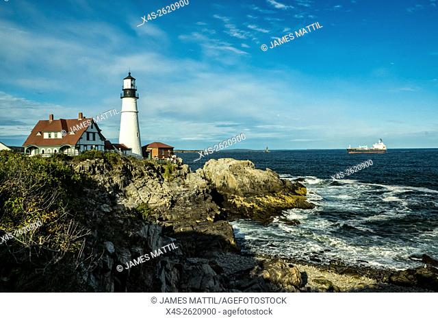 View of the landmark Portland head lighthouse in Maine as a ocean freighter approaches