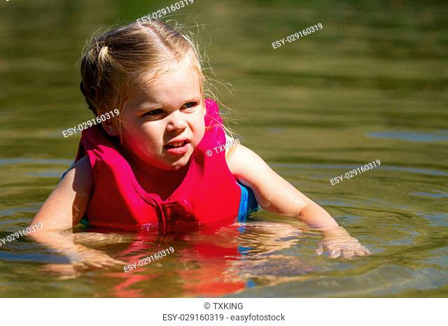 Girl is swiming in the water with her life vest on
