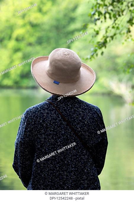 A woman with a brimmed hat looking out to a tranquil lake; Northumberland, England
