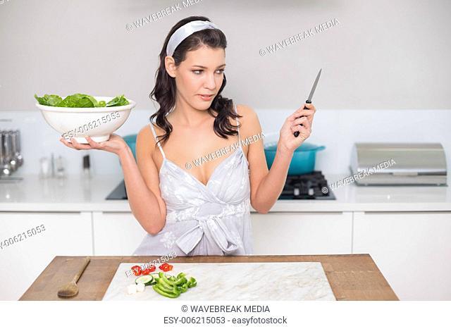 Pensive pretty brunette holding healthy salad