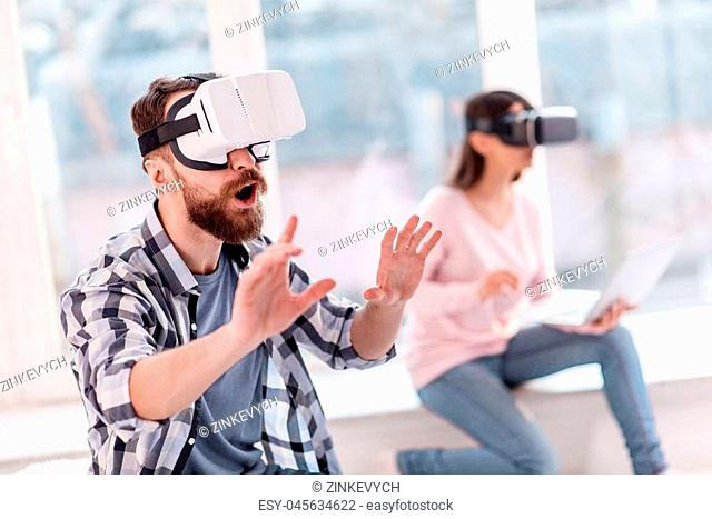 Something cool. Satisfied impressed handsome man stretching hands while shouting and wearing VR glasses