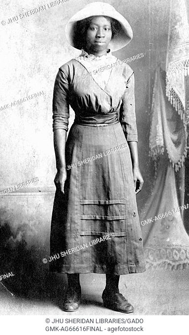 Portrait of an African American woman standing in front of a curtain, she is wearing a long dress which is cinched at the waist