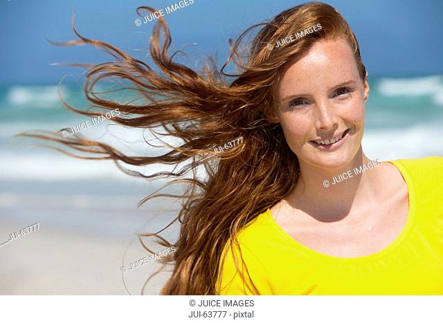 Portrait of smiling woman with red hair on sunny beach