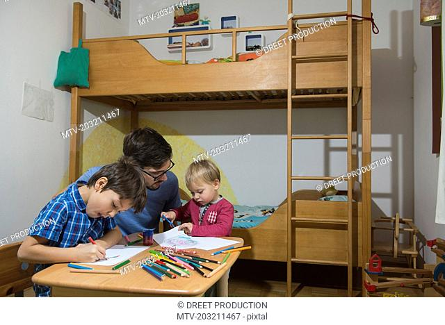 Brothers colouring with coloured pencils while father is assisting them, Munich, Germany