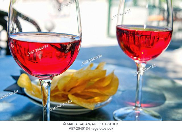 Spanish aperitif: two glasses of rose wine and chips on a terrace. Madrid, Spain