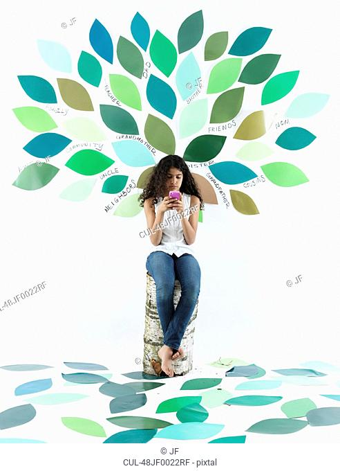 Girl using cell phone by tree on wall