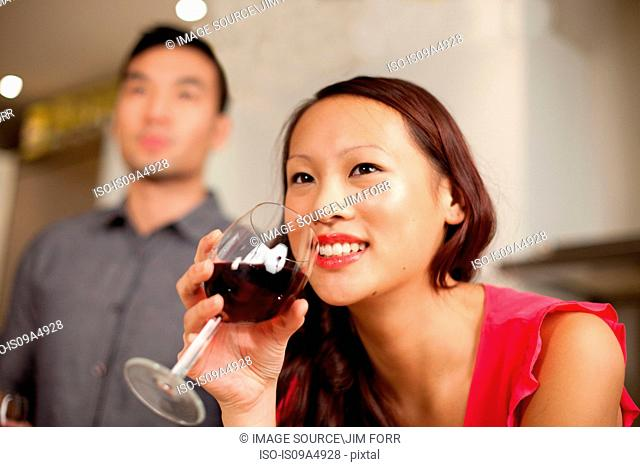 Woman drinking wine in kitchen