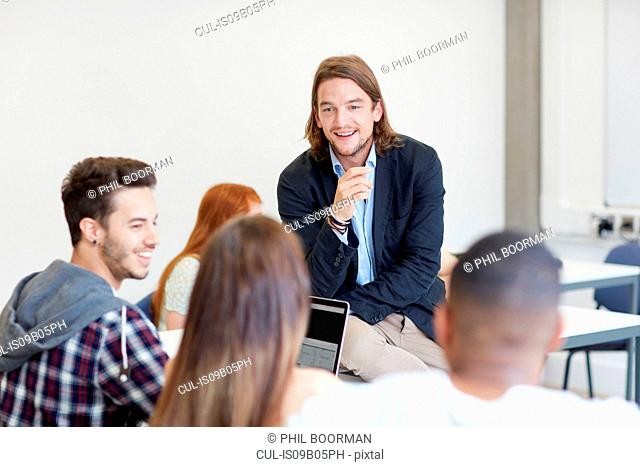 Male lecturer talking to students in higher education college classroom