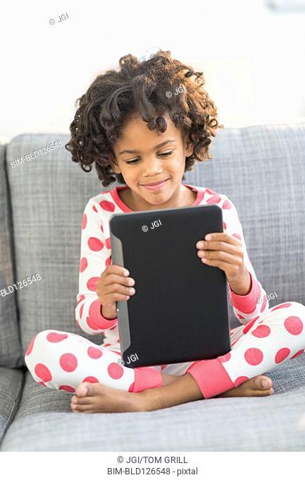 African American girl in pajamas using digital tablet on sofa