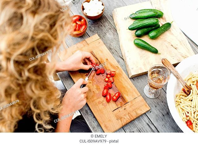 Woman chopping tomatoes on wooden chopping board, high angle
