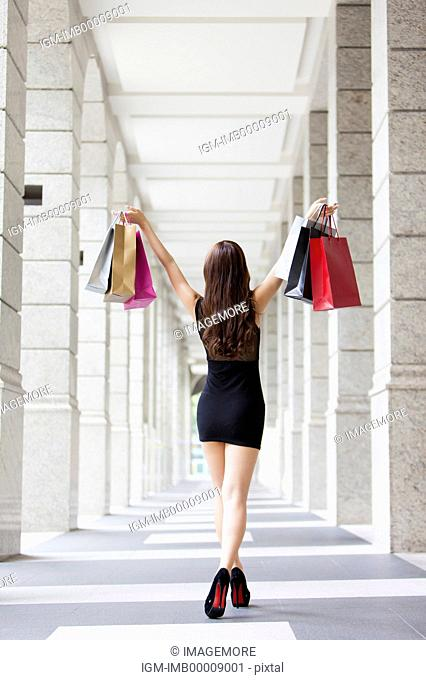 Young woman standing and holding shopping bags with rear view