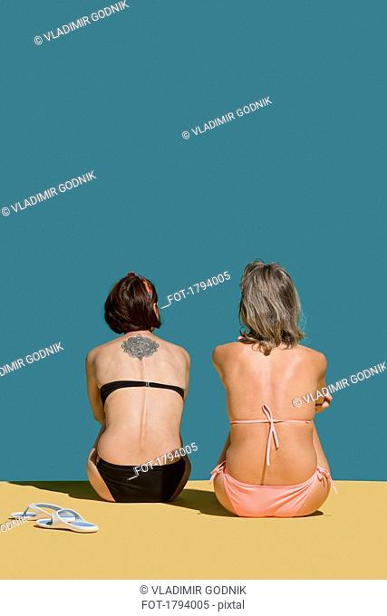 Women in bikinis sunbathing on green background