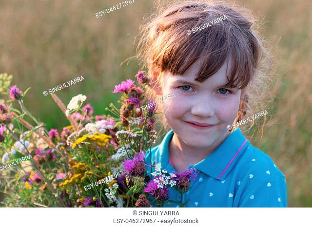 Little girl holds wild flowers and smiles in dry field at summer day