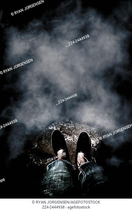 Dark atmospheric photo on the feet of a man standing on the edge of the unknown covered in a haze of mist and fog. What lies beneath