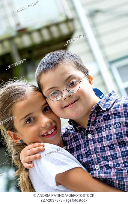 Older sister hugging and lifting younger brother with down's syndrome