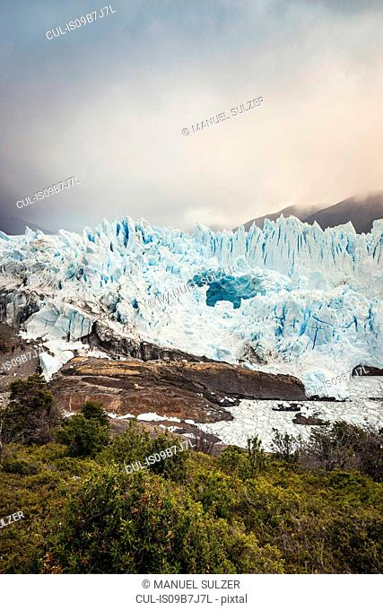 View of Perito Moreno Glacier and storm cloud over mountains, Los Glaciares National Park, Patagonia, Chile
