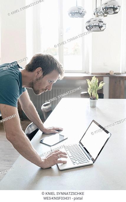 Man using laptop in a loft