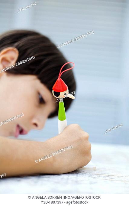 Child Writing with Pinocchio shape pen, focus on the pen