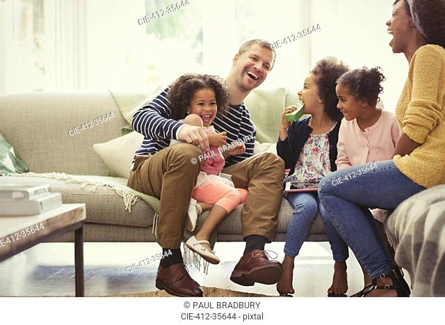 Multi-ethnic young family laughing on sofa