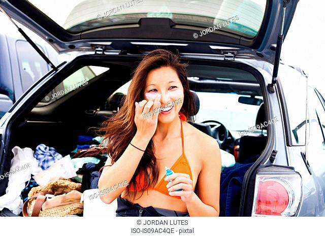 Woman putting on suncream, Hermosa Beach, California, USA
