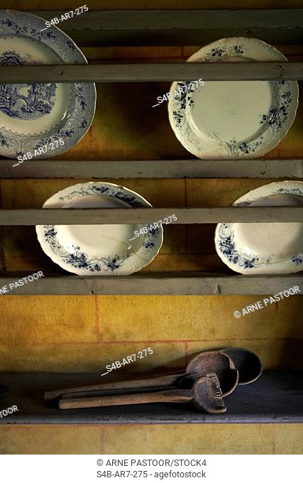 Outdated wooden spoons and china plates in kitchen shelf