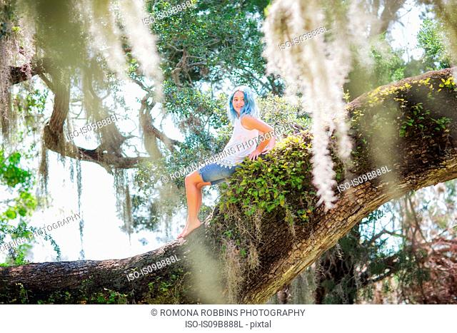 Girl sitting on old oak tree