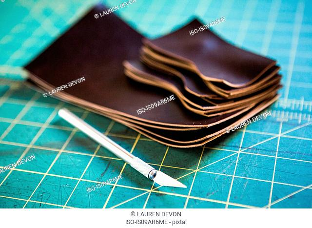 Stack of cut leather pieces and scalpel on cutting mat