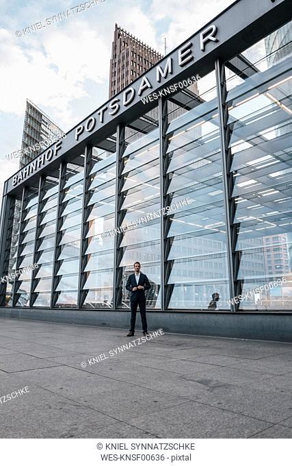 Germany, Berlin, Potsdamer Platz, businessman standing in front of train station