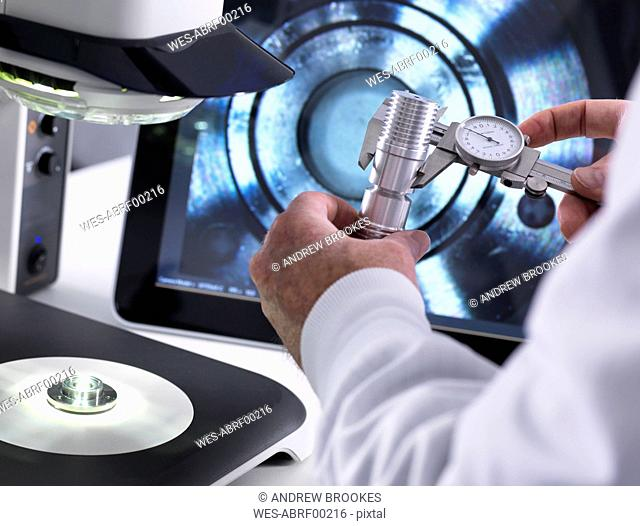 Engineer using a calliper and a 3d stereo microscope for quality control in the manufacturing of engineering components for industry