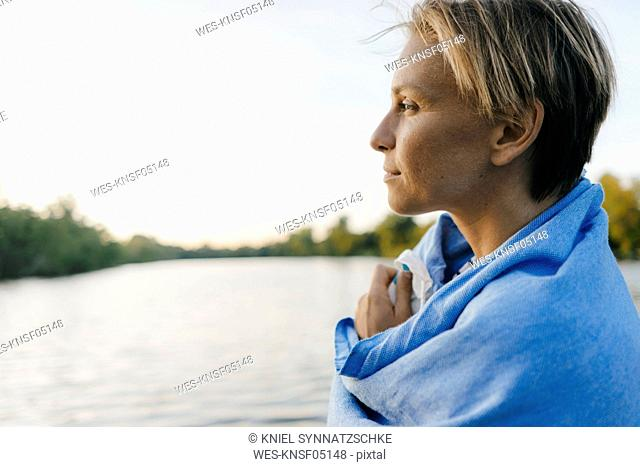 Portrait of woman wrapped in a towel at a lake