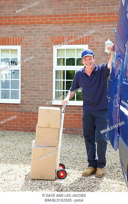 Caucasian delivery man wheeling packages near van