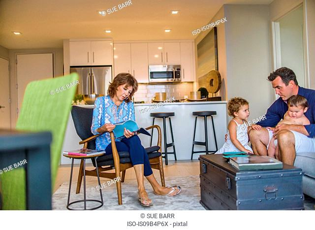 Father and two small children sitting on sofa, grandmother sitting in chair, looking through magazine