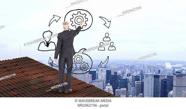 Businessman on roof drawing graphics in midair