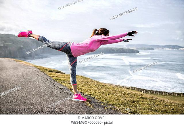 Spain, Gijon, sportive young woman exercising at the coast