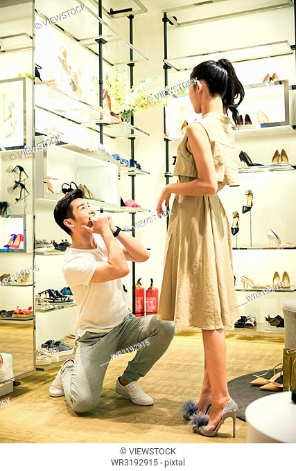 Young couples in the shoe store to try on shoes