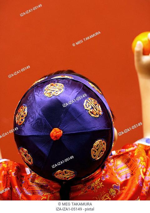 Rear view of a boy holding an orange