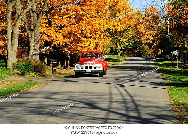Vintage red truck driving autumn country road