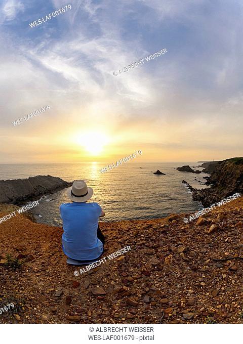 Portugal, Senior man sitting at bay watching sunset