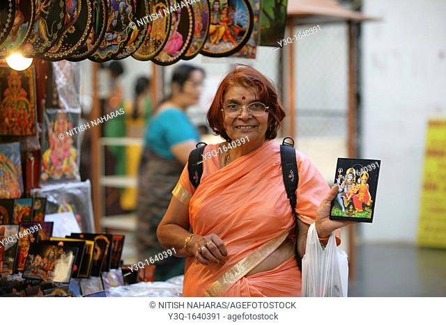 Elderly Hindu woman smiling and showing a picture of Gods Shiva and Parvati in Bangalore, India