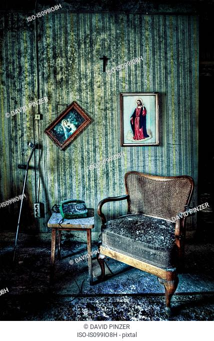 Abandoned room with chair and pictures