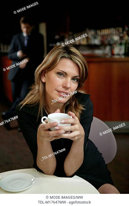 A young woman sitting in a hotel bar drinking coffee