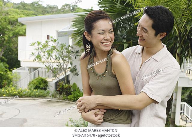 Man embracing woman, both smiling