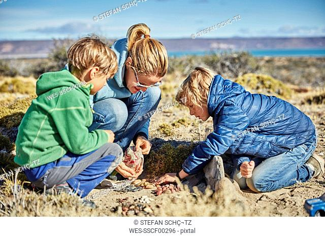 Argentina, Rio Chico, woman and sons collecting stones in the steppe